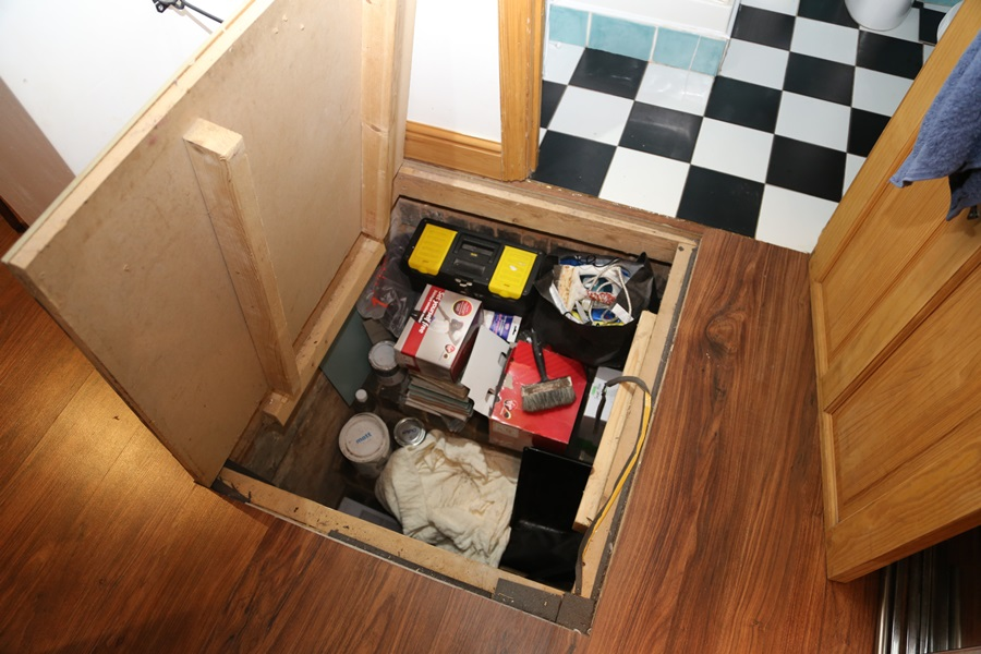 What looks like a small underfloor storage filled with tools and old paint cans – Source: Imgur/ demc7